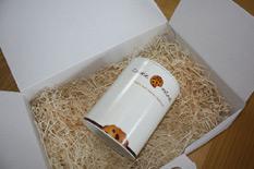 Weiße Cookiedose in einer hellen Pappschachtel